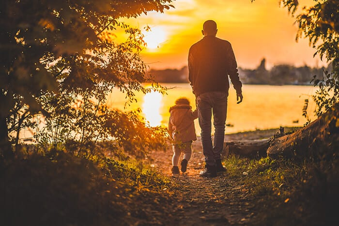 Father and daughter walking in the sunset