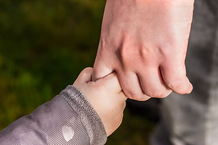 Parent holding their child's hand
